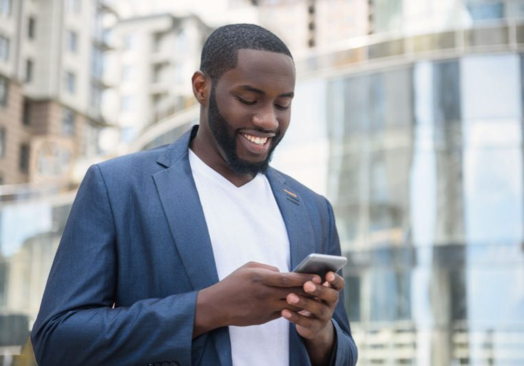 African businessman messaging in big city
