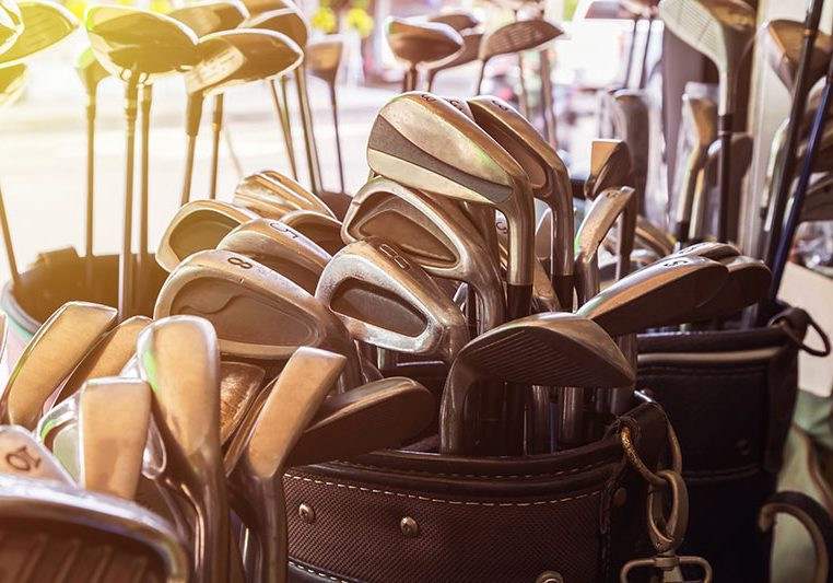 Professional image of large golf bags filled with dozens of high quality golf clubs